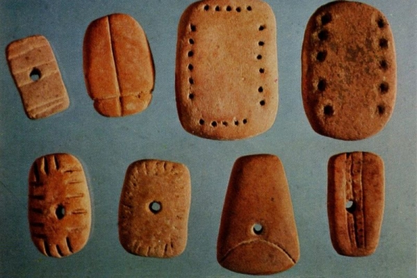 These perforated tokens with incised  rectangles were probably strung together.